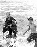My first award-winning photograph. The boy on the left had fallen from a dock. His jacket (discarded in the water) was water-logged, making it difficult to stay afloat. I provided the life preservers while other swimmers brought him safely ashore.