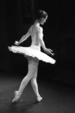 The stage lighting, graceful pose and costume are all that is needed to place this ballerina in context. If the audience or stage scenery had been included, the image would lose its simplicity.
