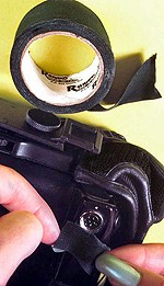 Black matte electrician's tape placed over shiny camera parts will prevent unwanted reflection.