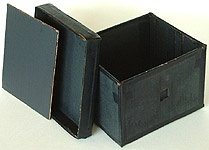 A  5 X 7 box pinhole camera with its light-proof inner lid and box top removed. The pinhole is located in the center of a brass shim that is painted black and covers the square opening in the camera's front panel.