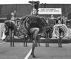 This photograph has its good points, but it lacks context. You wonder why the can-can dancers are performing in a parking lot. The viewer is missing information and the other elements tend to confuse the viewer.