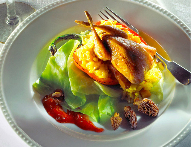 Quail served on a pumpkin risotto-stuffed red pepper and Boston lettuce, garnished with morel mushrooms.