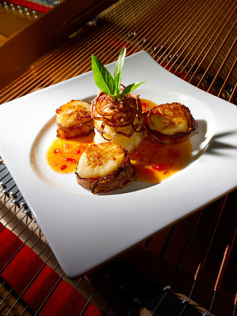 Bacon wrapped scallops with grilled onions on mashed potatoes, decorated with mint leaves, on a plate resting on piano strings.