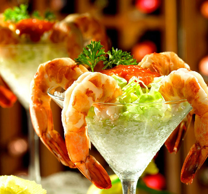 Semi-peeled jumbo shrimp cocktail on crushed ice in a martini glass with cocktail sauce and a sprig of parsley.