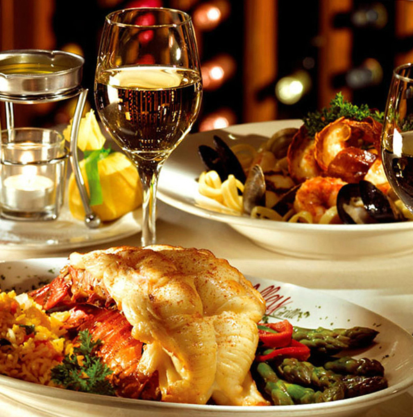 Split lobster tail on rice and asparagus with red pepper slices.