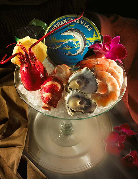 Tinned caviar surrounded by lobster parts, oysters on the half shell and shrimp on crushed ice in a martini glass.