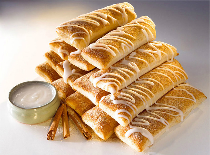 Stacked cinnamon bread sticks drizzled with vanilla icing beside a small bowl of icing dip and cinnamon sticks.