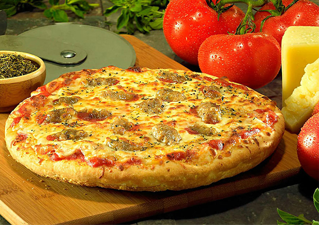 Thick crust sausage pizza surrounded by the flavor ingredients.
