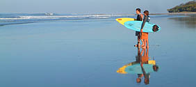 Early morning in Santa Teresa, Costa Rica,  two young surfers meet to assess the waves. Capturing their reflection in the vast expanse of shiny wet sand contributes to the composition.
