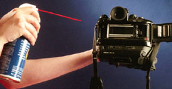 Keep the nozzle about 12-inches away from the camera and use short bursts