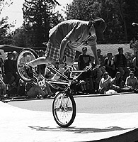 This trick rider's balancing act did not last long enough for a digital camera to capture it. A traditional film camera stopped the action at the precise moment the shutter button was pressed.
